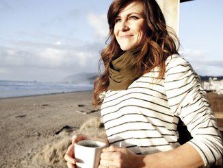 一位早起的女人,正在海边喝咖啡