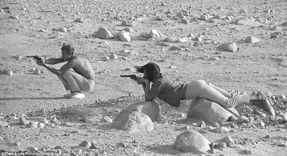 Steve McQueen and his wife, Neile Adams, firing pistols in the Palm Springs desert in 1963